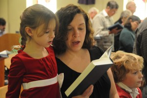 Mother and daughter with hymnal.